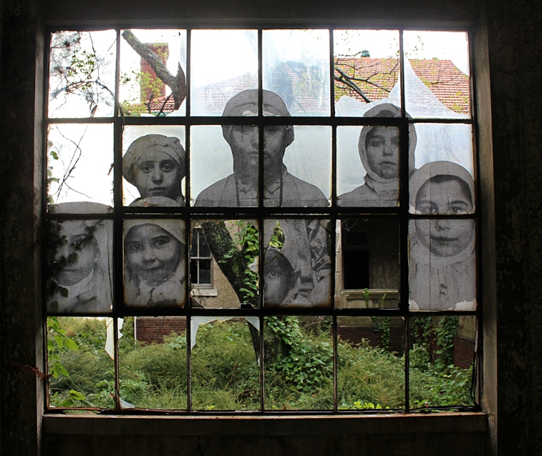 The faces of young immigrants peer through a shattered window.